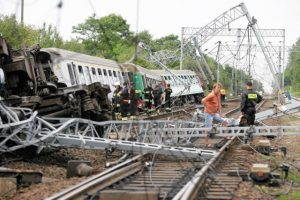 Emergency services personnel inspect the wreckage of a passenger train that derailed near the village of Baby